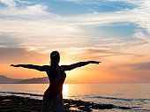 Healthy woman doing Yoga exercises on the beach in sunset time, Thailand