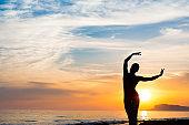 Sunset yoga woman meditation on Ocean coast