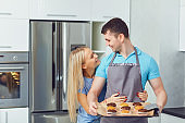 A young couple is baking cookies in the kitchen