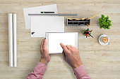 Man holding tablet knolling overhead view