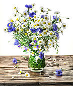 Bouquet of chamomiles and cornflowers in the vase.