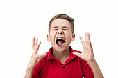 Portrait of furious little boy screaming in pain over white background