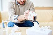 Crop depressed man tearing tissues