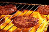 Hamburgers cooking on grill with flame