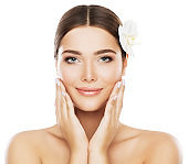 Face Beauty Skin Care, Woman Natural Make Up, Model Touch Cheeks by Hand, Flower in Hair, White Isolated