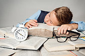 Child Sleep on Books, Tired Student Kid Studying, Boy Lying on Book near Alarm Clock, Children Education Concept