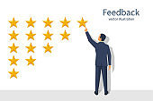 Star rating. Businessman holding a gold star in hand, to give five