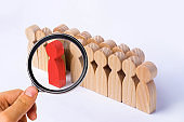 The chosen person among others. A human figure of red color stands out from the crowd. Wooden figures of people. A talented worker, a successful choice. Promotion. Concept of search for a worker.