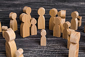 The child was lost in the crowd. A crowd of wooden figures of people surround a lost child. Lost, parents who have lost their parents are a small child. An orphan, a beggar, a lonely kid.