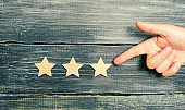 Universal recognition, success and high efficiency. Evaluation of the hotel or restaurant. Application in the market. The hand points to the third star on a dark background. Rating, level of quality.