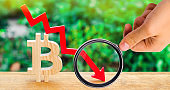 fall in the cost of bitcoin. Concept of a cryptocurrency market crisis. blockchain technology. wooden sign bitcoin and red arrow down.