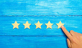 The businessman's hand points to the fifth star. A new star, achievement.The concept of the rating of hotels and restaurants, the evaluation of critics and visitors. Quality level, good service.