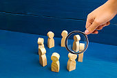 Communication. Business team, teamwork, team spirit. Wooden figures of people. Magnifying glass is looking at the People standing in a circle. A circle of people. The concept of discussion