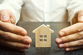 Insurance agent protects the house with a gesture of protection. The concept of property insurance protection and housing. Security and safety in the home. Life insurance and family. Real estate