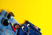 Woman's Things, Elegant Accessories . Jeans, lipstick, glasses, headphones. place for text. yellow background. summer. concept of fashion, style, lifestyle.