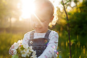 Baby with bouquet of flowers in the garden in sunlight. Cute happy summer blond girl in the garden. Apple blossom