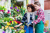 Beautiful woman buying freesias at the advice of a helpful vendor in a modern flower shop