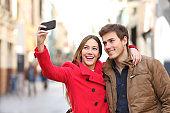 Happy couple taking selfies in the street in winter