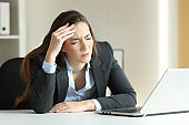 Businesswoman suffering migraine at office