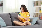 Happy teen using a mobile phone on a couch