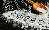 Word 'sweet' written in sugar on a black background.