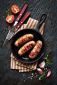 Grilled sausages or bangers in a vintage skillet
