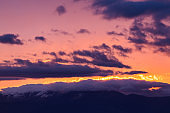 Majestic vivid sunset/sunrise with clouds over mountain rage