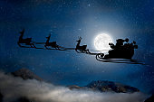 silhouette of a flying goth santa claus against the background of the night sky.