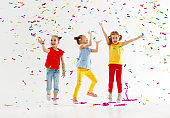 happy children on holidays  jumping in multicolored confetti on white