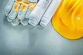Rolled blueprints hard hat safety gloves on concrete background