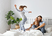 happy family mother, father and child  in bed