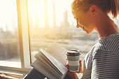 Happy young woman reads  book and drinks coffee in bed