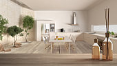 Wooden table top or shelf with aromatic sticks bottles over blurred modern kitchen with garden, white architecture interior design