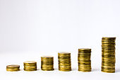 Six stacks of coin in ascending order on white gray background. Photo illustration of success in business and commerce, growth of revenue, investment, wage,  rising prices for goods, services