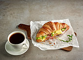 Croissant with ham and cheese on grey table