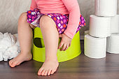 the girl sits on a green pot and learns basic hygiene