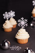 sweets for christmas - Christmas cupcake with cream cheese decorated with shining silver snowflakes on black background
