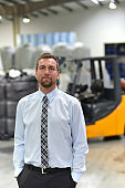 portrait of a manager in a logistics company - in the background a warehouse with chemicals and goods of a chemical factory
