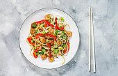Stir fry noodles with vegetables and shrimps on concrete background.