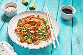 Stir fry noodles with vegetables and shrimps on wood background.