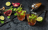Refreshing mojito cocktail with garnet, mint and lime, on a dark gray stone table with shaker for whipping drinks