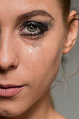 Sad crying girl looking into camera with smeared make-up