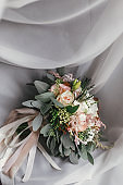 Stylish wedding bouquet of pink roses and green eucalyptus on background of sofa. Modern bride's bouquet on soft fabric in morning light. Wedding arrangements and decor