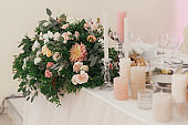 Stylish beautiful bouquets with roses and candles on pastel table at wedding reception in restaurant. Modern wedding setting. Wedding arrangements and decor