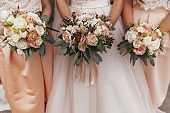 Gorgeous bride and beautiful Bridesmaids holding stylish wedding bouquets on background of modern  dresses. Wedding decorations