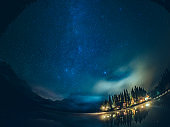Emerald lake with illuminated cottage under milky way