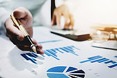 finance concept, business man analyze graph chart with using calculator and computer laptop for profit forecast in the future.