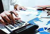 finance concept, business man holding pen using calculator with analyze graph chart  and computer laptop for profit forecast in the future.