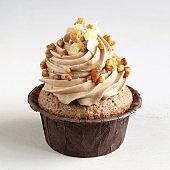 Chocolate cupcake with cream on dark background.
