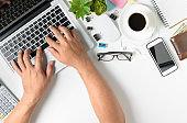 Hand man typing laptop on modern white office desk table